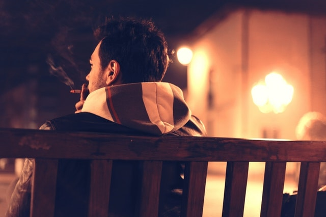 Man on Bench Smoking