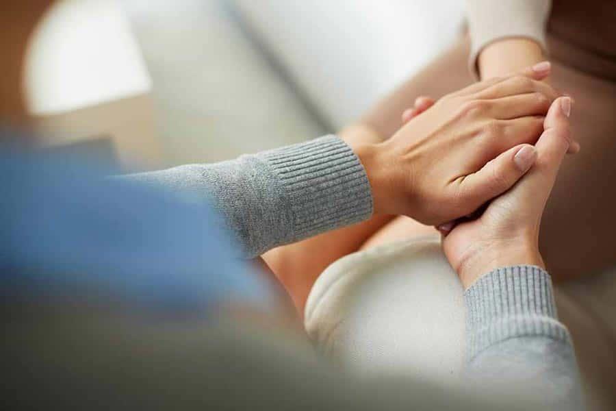 Caring staff holding the hand of a patient