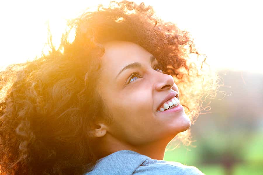 A young woman smiling into the sun